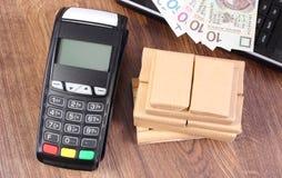 Terminale di pagamento con soldi, il computer portatile e le scatole polacchi sul pallet, pagando la spedizione ed i prodotti Fotografie Stock Libere da Diritti