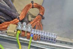 Terminales que ponen a tierra y alambres en cubículo de control eléctrico Imágenes de archivo libres de regalías