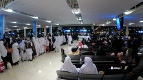 Terminalflughafen in Dubai Arabische Scheiche und Frauen im burqa gehen innerhalb des Anschlusses stock video