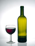 Terminando a garrafa - o vidro de vinho tinto e aproxima a garrafa vazia Fotografia de Stock