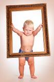 Terminante un niño pequeño que lleva a cabo el marco Fotografía de archivo libre de regalías