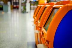 Terminaux pour l'enregistrement auto- se tenant dans la rangée à l'aéroport Images stock