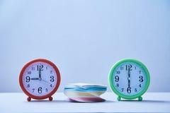 Termine della gestione di tempo e concetto di programma: pila di autoadesivi fra due orologi da tavolino fotografia stock libera da diritti