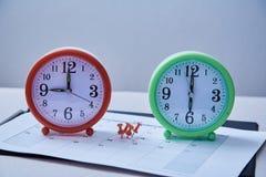 Termine della gestione di tempo e concetto di programma: a pressione rossi fra due orologi da tavolino immagini stock