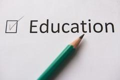 Termine o treinamento Para cumprir ajustou o objetivo a palavra EDUCAÇÃO é escrita no Livro Branco em lápis, marcado com tiquetaq imagens de stock