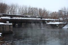 Termisk kraftverk som tömmer varmvatten in i behållaren arkivfoto