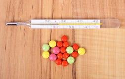 Termómetro y píldoras para los fríos, el tratamiento de la gripe y que moquea Fotografía de archivo libre de regalías