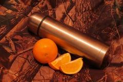 Termo de té con una naranja cortada Imagenes de archivo