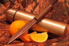 Termo de té con una naranja y un cuchillo cortados Imágenes de archivo libres de regalías