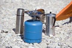 Termo del fabricante de café de la estufa que acampa del equipo que acampa en la tierra pedregosa Imagen de archivo