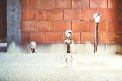 Termo isolamento con la schiuma dello spruzzo, i mura di mattoni e le linee di elettricità al cantiere Immagine Stock