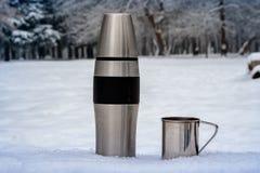 Termo y taza en el invierno al aire libre El ir de excursión foto de archivo