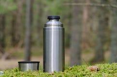 Termo y taza en una tierra cubierta de musgo Imagen de archivo libre de regalías