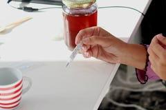 Termometer i händerna av en ung sjuk kvinna som har en tempera fotografering för bildbyråer