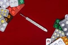 Termometer med preventivpillerar runt om och på en röd bakgrund arkivfoto