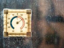 Termometer som är upplyst vid solen på smutsigt fönster fotografering för bildbyråer