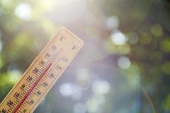 Termometer som pekar till himlen för att symbolisera värmen av sommar royaltyfri foto