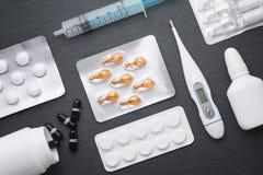 Termometern, minnestavlor för nasala droppar och ampuller med medicin på mörker kritiserar brädet Bästa sikt, lekmanna- lägenhet  Arkivfoton