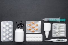 Termometern, minnestavlor för nasala droppar och ampuller med medicin på mörker kritiserar brädet Bästa sikt, lekmanna- lägenhet, Arkivfoto