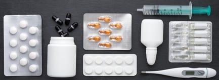 Termometern, minnestavlor för nasala droppar och ampuller med medicin på mörker kritiserar brädet Bästa sikt, lekmanna- lägenhet  Royaltyfri Bild