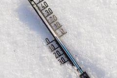 Termometern på snö visar låg temperatur Arkivbild
