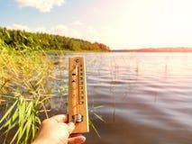 Termometervisning som 30 grader är celsius av värme mot bakgrunden av sjövattnet och den blåa himlen i solljus royaltyfri foto