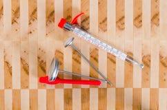 Termometri della cucina su un tagliere Fotografie Stock