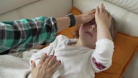 Termometro del primo piano Temperatura di misurazione della madre del suo bambino malato Bambino malato con febbre alta che si si archivi video