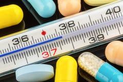 Termometro e pillole Fotografie Stock Libere da Diritti