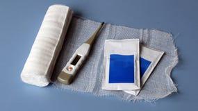 Termometro, garza sterile e due borse delle droghe Fotografie Stock