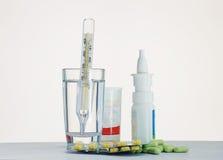 Termometro in un bicchiere d'acqua e farmaco per la tavola Fotografia Stock Libera da Diritti