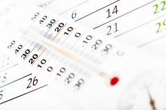 Termometru obsiadanie na kalendarzowym prześcieradle Obrazy Stock