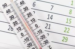 Termometru obsiadanie na kalendarzowym prześcieradle Obrazy Royalty Free
