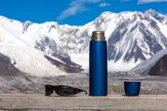 Termos blu di viaggio con la tazza e gli occhiali da sole aperti sulle alte montagne di legno della Tabella su fondo Immagini Stock