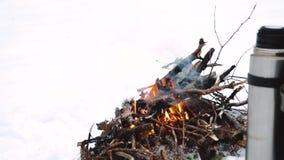 Termos z gorącą herbatą, kawa Obozowy ogień w zima czasie, otaczającym śnieżnym lasowym pojęcie przygody aktywnym być na zdjęcie wideo