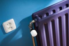 Termostat på ett purpurfärgat element och en blå vägg fotografering för bildbyråer