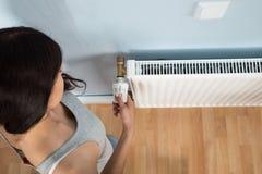Termostato de giro da jovem mulher no radiador Imagem de Stock Royalty Free