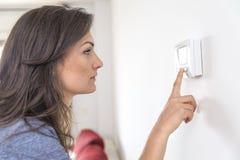 Termostato digitale del bello pulsante della donna alla casa Immagini Stock Libere da Diritti