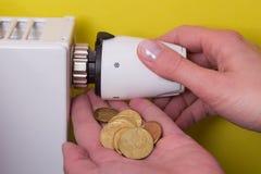 Termostato do radiador, moedas e mão - amarelo Foto de Stock