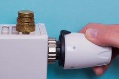 Termostato do radiador, moedas e mão - azul Fotos de Stock