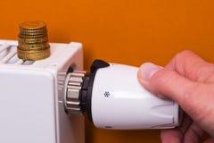 Termostato do radiador, moedas e mão - marrom Fotos de Stock