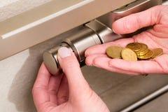 Termostato, moedas e mão do radiador Imagens de Stock Royalty Free