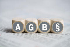 Terms and Conditions (as acronym AGB in German). On cubes on a newspaper Royalty Free Stock Image