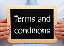 Terms and Conditions - Manager holding chalkboard with text. In his hands stock photo