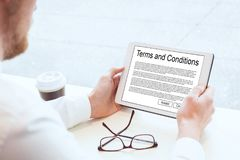 Terms and conditions. Business man reading on tablet Stock Photography