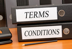 Terms and conditions. Text 'terms and conditions' in uppercase black letters on two white labels attached to two binders placed on a wooden office desk with Royalty Free Stock Photo
