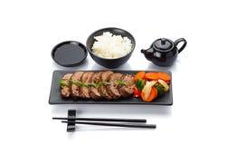 Ternera asada con las verduras en una placa negra con la salsa de soja del arroz Imágenes de archivo libres de regalías