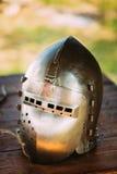 Terno de Helmet Of Medieval do cavaleiro de armadura na tabela Fotografia de Stock