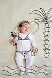 Terno de natação vestindo do bebê que encontra-se na praia sob as palmas fotografia de stock