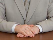Terno desgastando do homem de negócios com as mãos clasped imagem de stock royalty free
